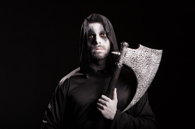 Böser sensenmann mit einer axt über schwarzem hintergrund für halloween.
