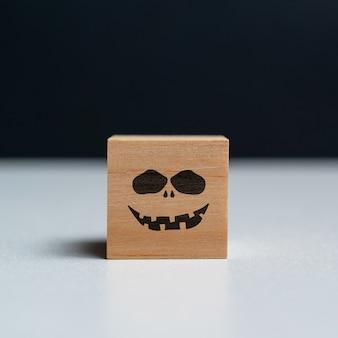 Böses gesicht auf einem hölzernen würfelhalloween-urlaub