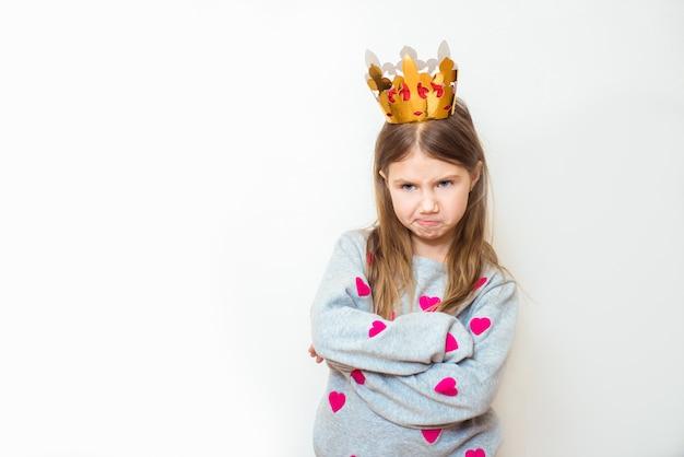 Böses kind mädchen mit einer krone auf einem weißen