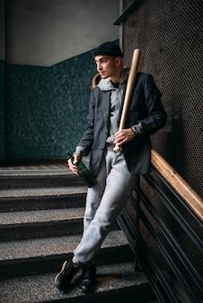 Bösewicht mit baseballschläger und flasche bier auf der treppe stehend. straßenräuber wartet auf opfer. verbrechenskonzept