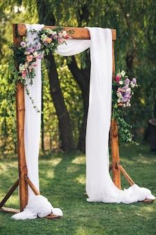 Bogen für die hochzeitszeremonie, dekoriert mit stoffblumen und grün, befindet sich im park.