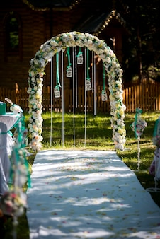 Bogen für die hochzeitszeremonie. mit blumen und viel grün dekoriert. befindet sich in einem pinienwald. frisch verheiratet. hochzeitsdekor.