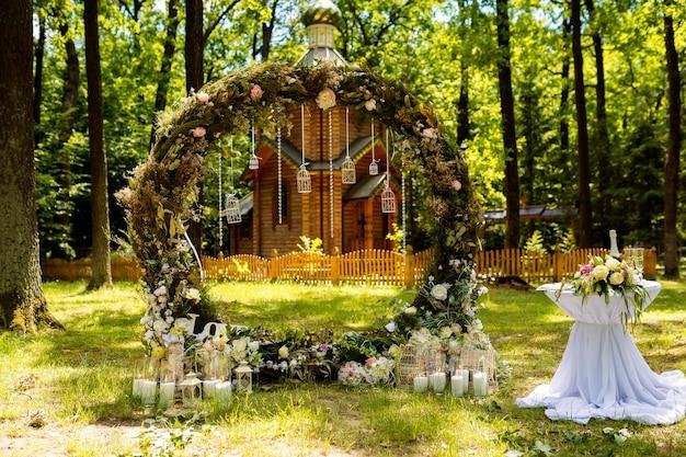 Bogen für die hochzeitszeremonie. mit stoffblumen und viel grün dekoriert. befindet sich in einem pinienwald.