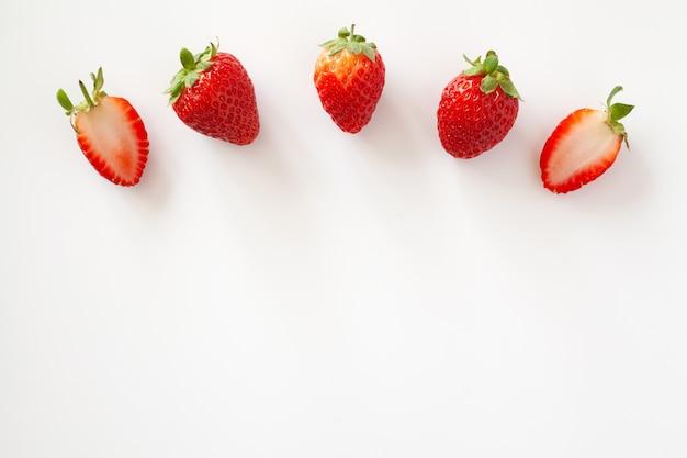 Bogen von ganzen und halben erdbeeren auf weißer oberfläche. isoliert. speicherplatz kopieren.