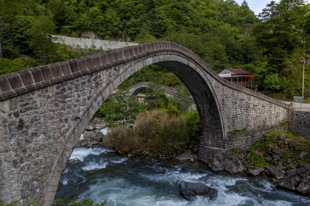 Bogenbrücke über einem fluss, umgeben von wäldern in arhavi in der türkei