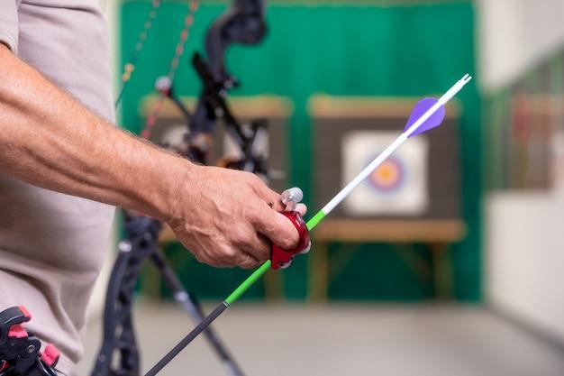 Bogenschütze, der den bogen auswählt einen pfeil bereit hält, zum ziel zu schießen