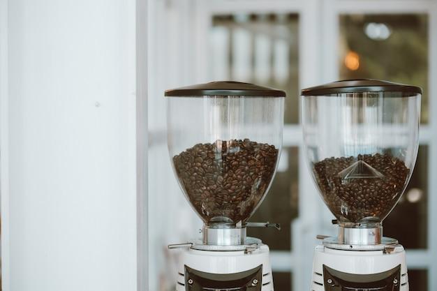 Bohnen kaffee auf behälter oben auf der mühle, die kaffeebohnen hält