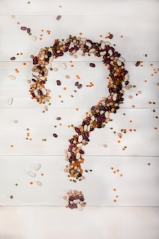 Bohnen, linsen, erbsen ausgebreitet auf einem weißen hölzernen hintergrund in form eines fragezeichens