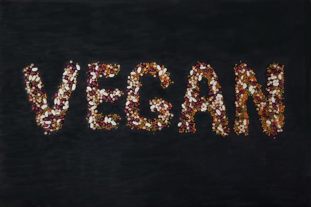 Bohnen, linsen, mungobohnen, erbsen auf einem schwarzen hölzernen hintergrund in form der inschrift vegan ausgebreitet