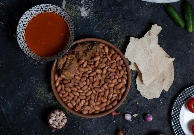 Bohnen mit fleisch und tomatensauce in einer schüssel. mit lavash und gemüse, zwiebeln, gurken