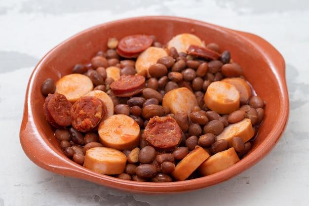 Bohnen mit geräucherten würstchen und würstchen in keramikschale