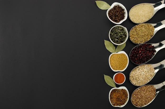 Bohnen-reis-buckwheat samen linsen-gewürze in den löffeln auf einem schwarzen hintergrund