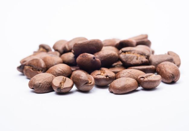 Bohnenkaffee im weißen hintergrund. mittel geröstete kaffeebohnen haben eine hellbraune farbe auf weißem hintergrund.
