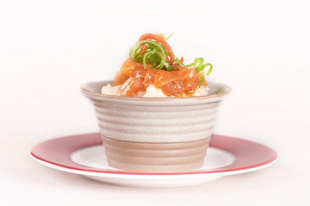 Bohnenpüree mit süßer zwiebel und tomatensauce, serviert in einer schüssel auf einem roten und weißen teller