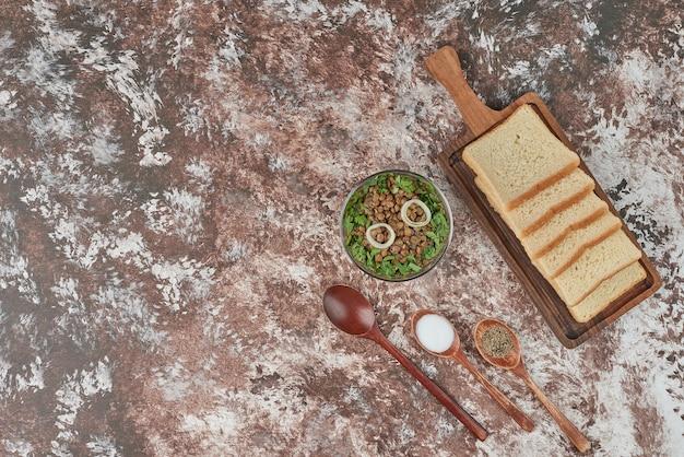 Bohnensalat mit brotscheiben und gewürzen.