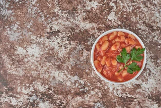 Bohnensuppe auf tomatensauce in einer weißen tasse