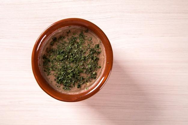 Bohnensuppe in der schüssel auf hölzernem tischhintergrund