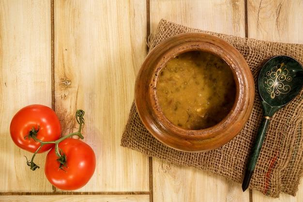 Bohnensuppe in einem traditionellen topf auf einem bretterboden.