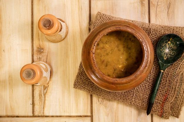 Bohnensuppe in einem traditionellen topf auf einem holztisch. von oben betrachten.