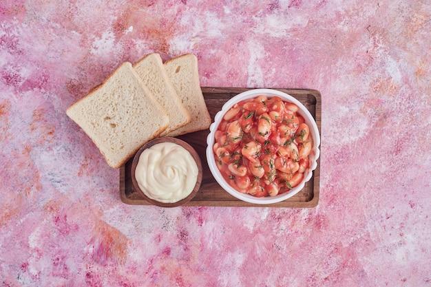 Bohnensuppe in tomatensauce in einem weißen teller mit brotscheiben und mayonnaise.