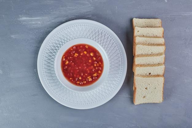 Bohnensuppe in tomatensauce mit brotscheiben.