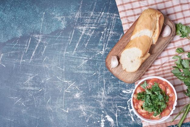 Bohnensuppe mit kräutern und weißbrot, draufsicht.