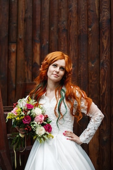 Boho braut mit roten haaren posiert