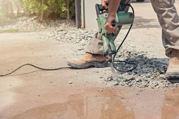 Bohrende betonfahrstraße der arbeitskraft mit jackhammer.