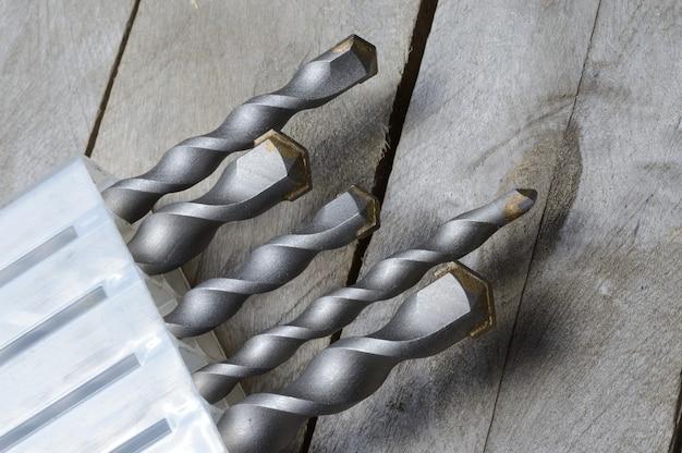 Bohrer mit hartmetallbestückten hammerbohrern liegen in einem kunststoffkoffer auf einem plankenholzhintergrund. nahaufnahme.