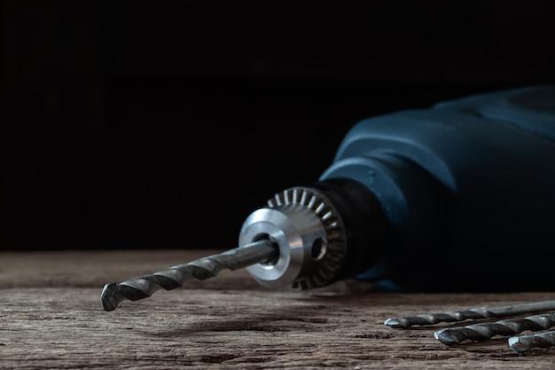 Bohrgerät und satz des bohrgeräts auf holztisch, tischlerwerkzeuge, hauptreparaturkonzept
