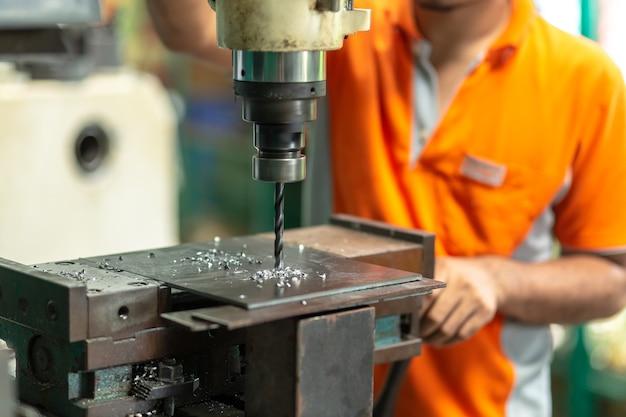 Bohrmaschine, mitarbeiter bohrmaschine in flachstahl platte mit tischbohrmaschine.
