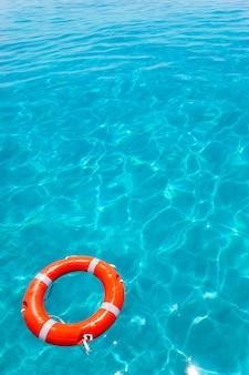 Bojenorange, die in perfekten tropischen strand schwimmt
