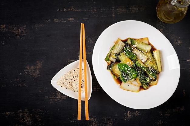 Bok choy gemüse unter rühren mit sojasauce und sesam braten. chinesische küche. ansicht von oben