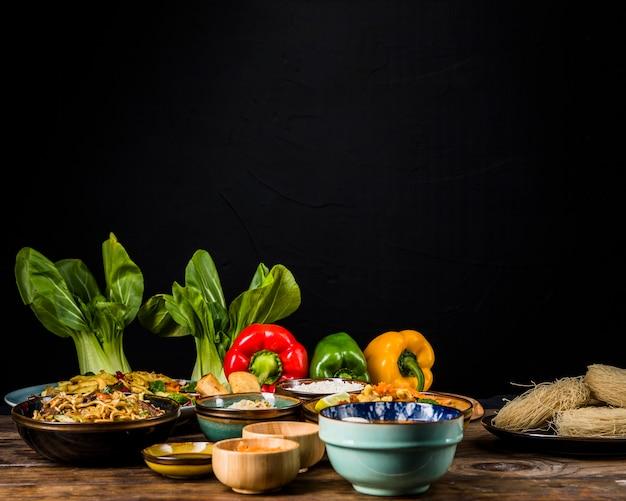 Bokchoy; paprika und thailändisches traditionelles essen auf tisch vor schwarzem hintergrund