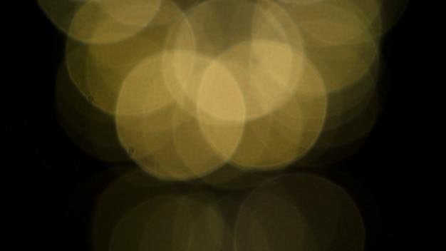 Bokeh-bilder kreisen blasen in gelber farbe auf schwarzem hintergrund ein.