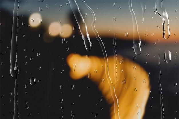 Bokeh-lichter nachts durch fenster mit regentropfen