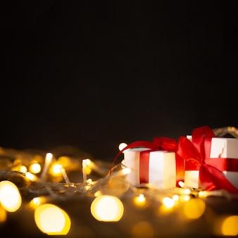 Bokeh lichter und weihnachtsgeschenke auf schwarzem hintergrund