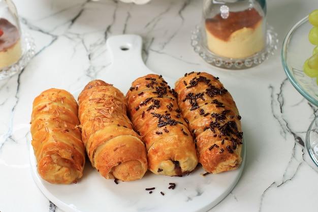 Bolen lilit oder bananenrollen von bread.co bandung bakery. gebäck mit bananenfüllung, bestreut mit schokolade oder geriebenem käse. serviert auf weißem marmortisch