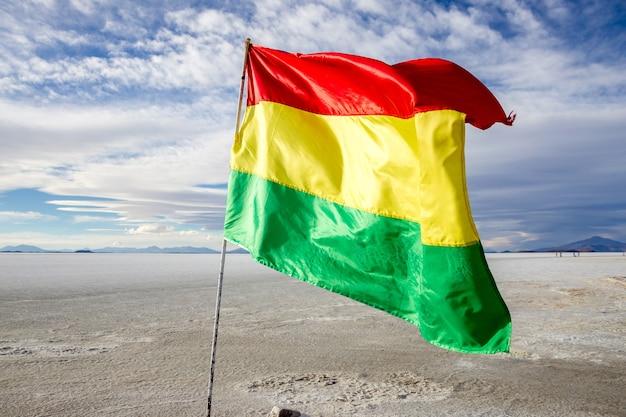 Bolivianische flagge, die im wind in salar de uyuni flattert