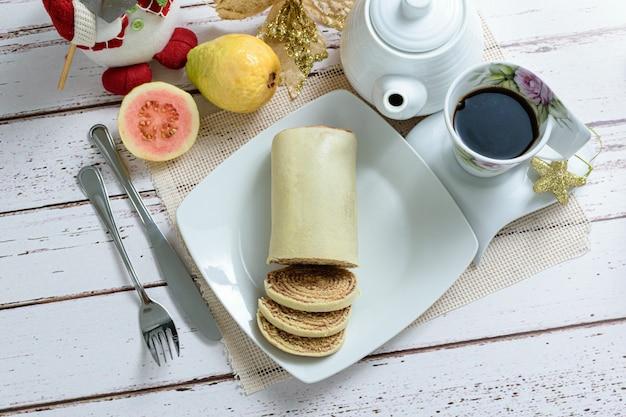 Bolo de rolo (brötchenkuchen) in scheiben geschnitten neben besteck, tasse kaffee und guaven, draufsicht.