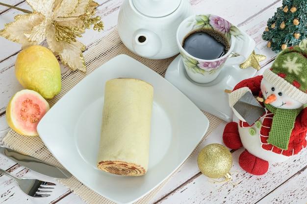 Bolo de rolo rollkuchen neben einer weihnachtsdekoration traditionelle brasilianische süße draufsicht.