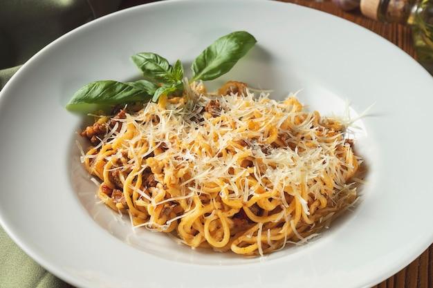 Bolognese pasta mit roter sauce, parmesan, parmesan und hackfleisch.