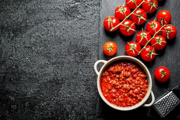Bolognese-sauce in schüssel mit kirschtomaten. auf rustikalem hintergrund