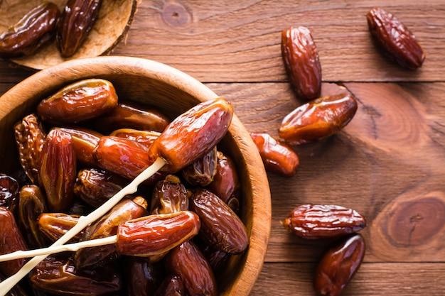 Bonbon getrocknete dattelfrüchte in einer hölzernen schüssel auf dem tisch. ansicht von oben