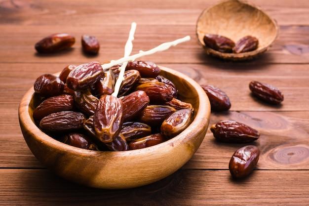 Bonbon getrocknete dattelfrüchte in einer hölzernen schüssel auf dem tisch
