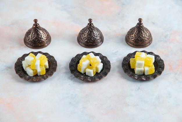 Bonbongeschirr und gelbe bonbons in einer reihe über weißer oberfläche