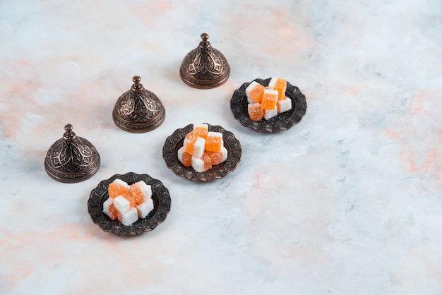 Bonbongeschirr und orangefarbene bonbons in einer reihe über weißer oberfläche