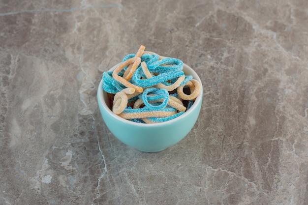 Bonbons mit blauem band. bunte geleebonbons in blauer schüssel über grauer oberfläche.