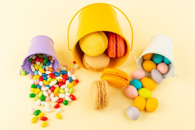 Bonbons und macarons der draufsicht, die auf dem gelben schreibtischkuchen-kekszuckersüßbacken bunt sind