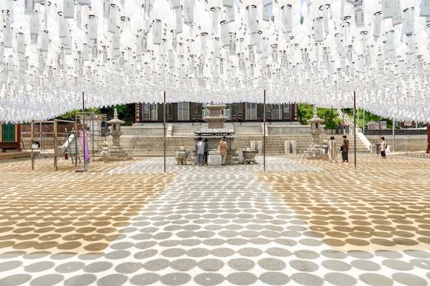 Bongeunsa tempel während der sonnigen tageszeit unter weißen laternen und buddhisten beten zu buddha